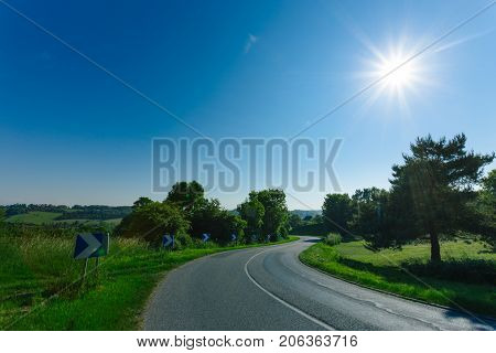 Empty Asphalt Curvy Road Passing Through Green Fields And Forest. Countryside Landscape On A Sunny D
