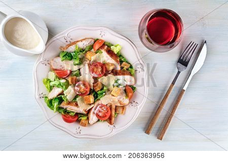 An overhead photo of a plate of chicken Caesar salad on a light background with a gravy boat, a fork and a knife, a glass of wine, and copy space
