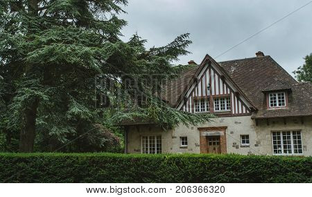 Country House With Green Fence And Garden A Spruce Tree In The Region Of Normandy, France. Beautiful
