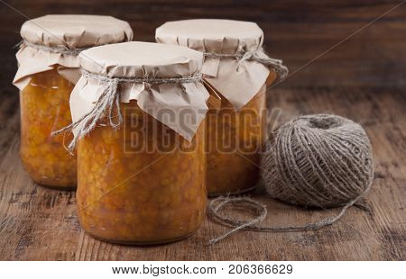 Wet cloudberry in cans on an old wooden table