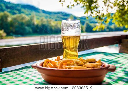 Glass of beer and french fries on the restaurant table at river view food and drink on the table