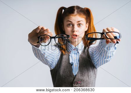 funny red-haired girl with two tails holds in her hands two pairs of glasses