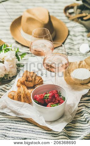 French style romantic summer picnic setting. Flat-lay of glasses of rose wine with ice, strawberries in bowl, croissants, brie cheese, straw hat, peony flowers, square crop. Outdoor gathering concept