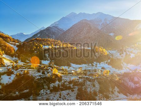 small village located in the valley at the foot of mountains a mountain ridge snow tops evening the sun lights the valley beautiful autumn paints