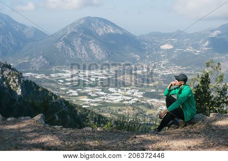 The man sitting a hill and looks at the unleashed landscape. Seascape with a bird's-eye view