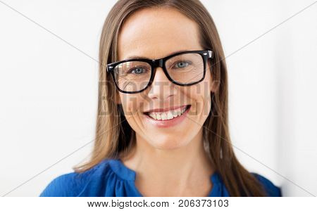 people, office and vision concept - close up of happy smiling middle aged woman in glasses