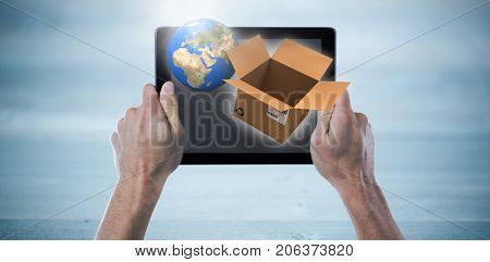 Cropped hand holding digital tablet against bleached wooden planks background