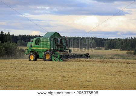 SALO FINLAND - AUGUST 25 2017: Farmer harvests grain with John Deere Combine 9460i on an autumn evening in rural South of Finland.