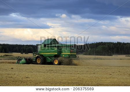 SALO FINLAND - AUGUST 25 2017: Grain harvest with John Deere Combine 9460i on an autumn evening in rural South of Finland.