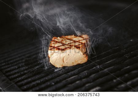 Medium rare grilled meat on hot cook closeup view. Steak with smoke preparing on cooker, juicy roasted beef with proteins in stove