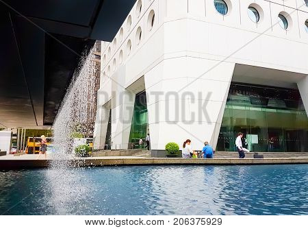 HONG KONG ASIA - SEPTEMBER 20 2017; Jardine House 1 Connaught Place Central Hong Kong with water feature at base being enjoyed by people, mobile phone image.