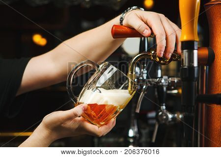 Barman pours beer into a glass goblet from the tap, light alcoholic drink with foam in transparent mug, closeup hands of male near bar counter