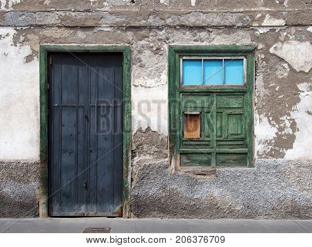 empty derelict small house with decaying bricks broken plaster and green windows with fading colors and black wooden door