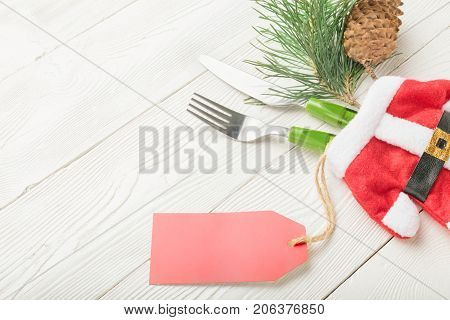 Christmas dinner table setting price concept. Fork, knife, green fir decor with blank price tag on white wooden background