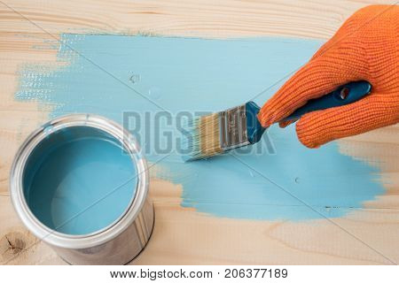 Home improvement paint brush and opened can of blue paint. worker paints board. employee paints the a wooden table.