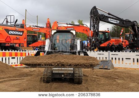 HYVINKAA FINLAND - SEPTEMBER 8 2017: Operator sifts sand with land leveler mounted on Bobcat T450 Compact Track Loader on a sand work site on Maxpo 2017.