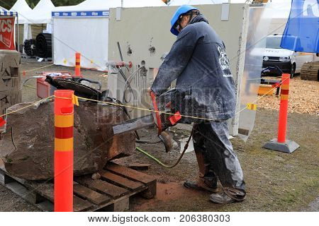 HYVINKAA FINLAND - SEPTEMBER 8 2017: Man saws natural granite stone with ICS chain saw on Maxpo 2017.