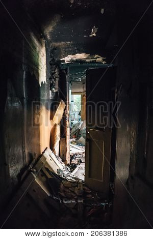 Dark corridor in burned ruined house building after disaster, war, earthquake, Hurricane or other natural cataclysm, vertical image