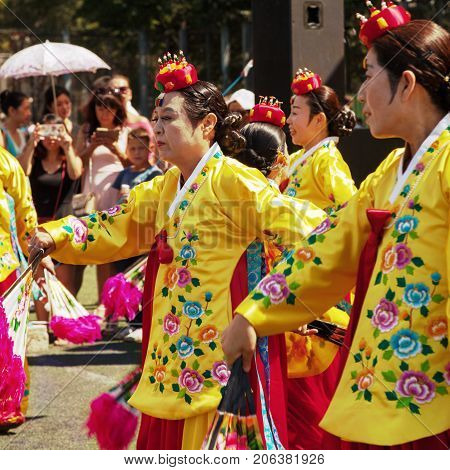 Khabarovsk Russia - August 13 2017: Korean traditional dancers. Old ladies wearing colorful yellow and pink dresses dancing Buchaechum or fan dance
