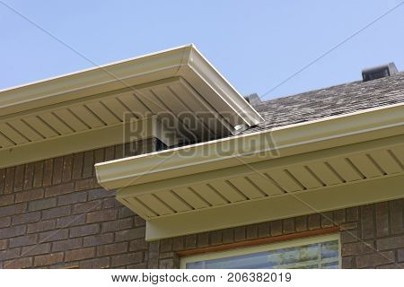 Roof Showing Gutters And Soffit On The Back Of A Brick House.