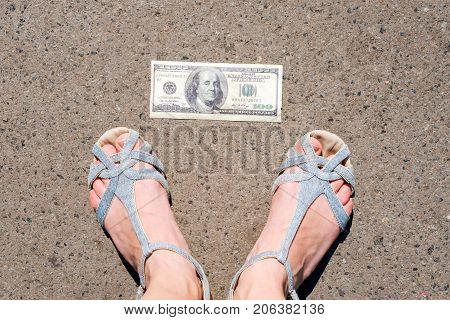 Lucky woman finding money on the street. Women feet next to hundred dollar bill. Lost and found money lying down on asphalt road