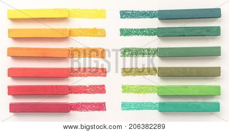 Close up view of bright colorful pastel chalks and their pigments on white background