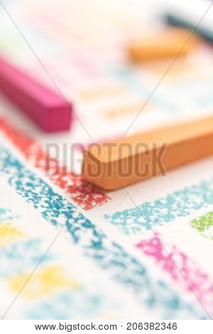 Cropped photo of pieces of chalk, over abstract colorful background