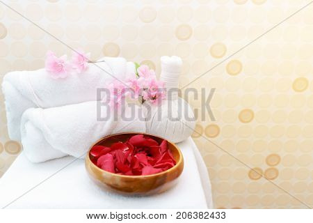 White towel rolls on top with pink flower and Thai Herbal Compress prepared on massage table for spa treatment