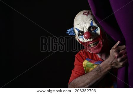 closeup of a scary evil clown peering out from a purple stage curtain, with a blank black space on the left