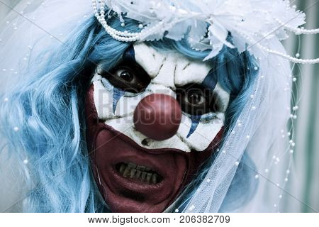 closeup of a scary evil clown wearing a bride dress, with a veil and a diadem