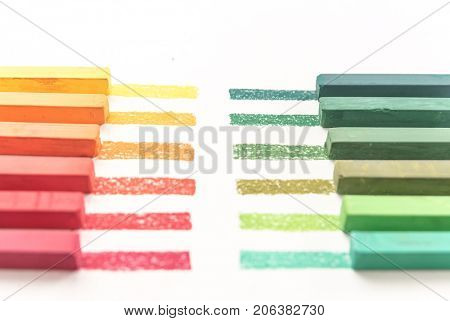 Cropped photo of colorful pastel chalks and their pigments on white background