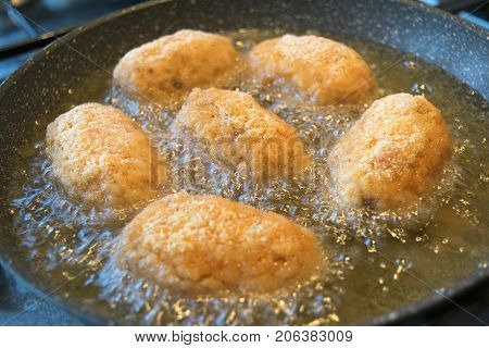 cooking rice croquettes or arancine in pan with olive oil