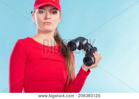 Lifeguard woman supervising swimming pool water with binoculars on blue. Accident prevention and rescue.