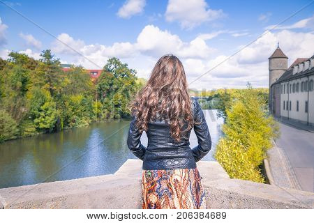 Young woman with the backside at the camera on the edge of a bridge watches towards the horizon meditating in Schwabisch Hall Germany.