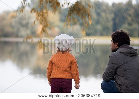 Man and little girl walking together in the park looking at the lake fall outdoors autumn day. Single parent. Family relationships.