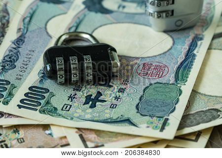 selective focus on combination lockpad on pile of japanese yen banknotes as financial safe haven or security concept.
