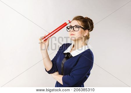 Student looking woman wearing nerdy eyeglasses holding big oversized pencil thinking about something.