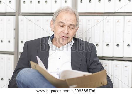 Senior man with white shirt sits at a desk, scrolling in a document file