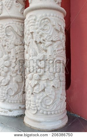 Two white columns with bas-reliefs in the form of plants against a red wall in perspective
