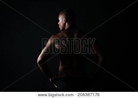 Portrait of young afroamerican sports man, standing back, looking aside, isolated on black background poster