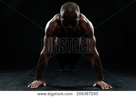 Portrait of youg afro american sports man doing pushup exercise, on black background