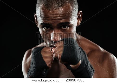 Close-up portrait of young afroamerican boxer, showing his fists with boxing bandage, looking at camera, over black background