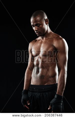 Young afro american boxer, looking down, isolated on black background