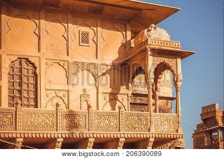 Example of Indian architecture with details of facade of historical house, carved walls, balcony and traditional elements.
