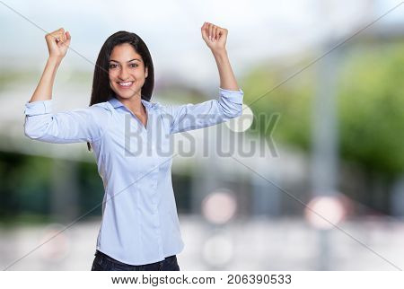 Cheering arabic businesswoman reaching hand outdoor in front of an office building