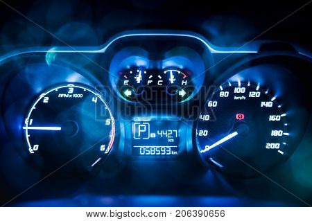 Dashboard. Close up of car speed meter. Car instrument panel interior lights with colorful bokeh.