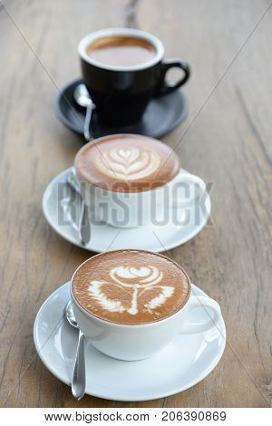Three Cofffee Cup With Latte Art Rose Flower Shape In The First Cup Another Cup Is Hearth And Leaf P