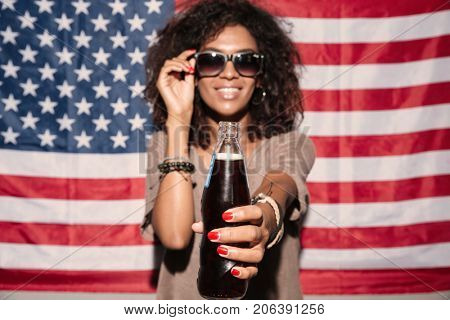 Picture of happy african young lady wearing sunglasses standing over USA flag drinking aerated water. Looking camera.
