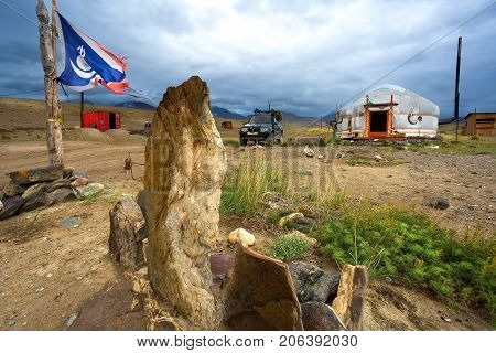 White national Yurt Mongolia in the natural world. In the foreground decorative rocks and a national flag in blue and white colors.