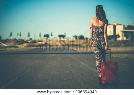 Woman walking on the road Travel dragging a suitcase. Efect vintage. Copy Space poster